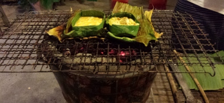 Making a meal the slow and old-fashion way. Banana leaves are used instead of a metal pan or pot.