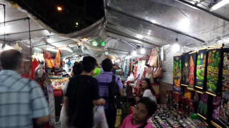 Street vendors line up both sides of the sidewalk. The tarp is used to provide cover for rain which is very common in Bangkok.
