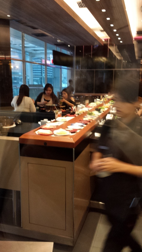 Conveyor belt moves raw food to customers. You cook it in your personal hot pot.